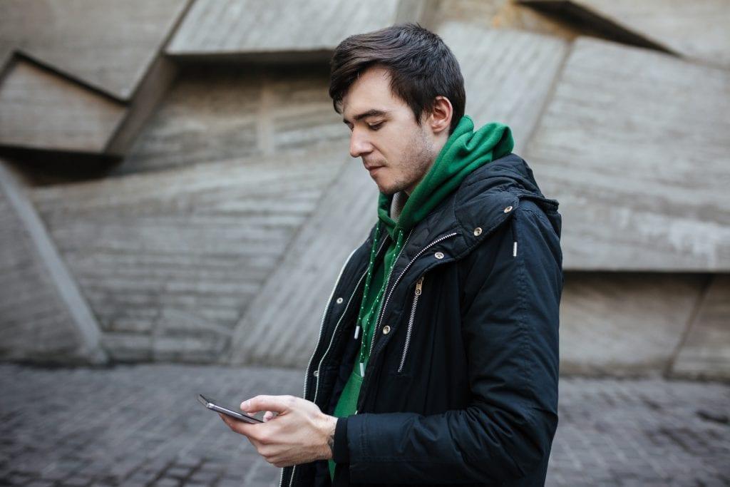 Hombre caminando por la calle con un teléfono en la mano